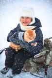 Little girl and a red cat on the sleigh. Royalty Free Stock Image