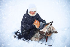 Little girl and a red cat on the sleigh. Stock Images