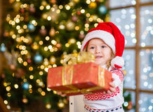 Little girl in a red Christmas hat gives a gift Royalty Free Stock Images