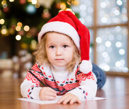 Little girl in a red Christmas hat writing a letter to Santa Cla Stock Photography