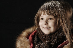 Little girl in a red coat looking at the falling snow. Snowfall. Royalty Free Stock Images
