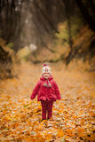 Little girl in red coat at scenic fall park Royalty Free Stock Image