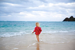 Little girl in red coat staying in the water on the beach Royalty Free Stock Images
