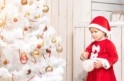 Little girl in red costume decorates new year tree with ball. In decorated room Stock Photography