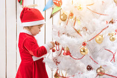Little girl in red costume decorates new year tree with ball. In decorated room Stock Images