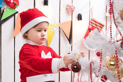 Little girl in red costume decorates new year tree with ball. In decorated room Stock Image