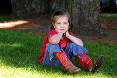 Little girl with red cowboy boots. A little 4 yr old girl in the park wearing red cowboy boots, sitting in the grass, bored royalty free stock images