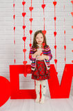 Little girl with red decoration for Valentines Day Stock Images