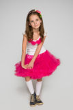 Little girl in a red dress against the gray Royalty Free Stock Photos