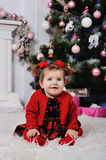 Little girl in a red dress on  background of the Christmas tree. Baby girl with red ribbons sitting on the background of the Christmas tree and smiling Stock Photo