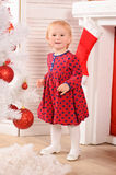 Little girl in red dress in christmas interior Stock Images