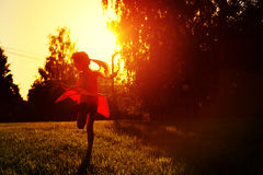 Little girl in a red dress dancing in the sunset Stock Photo