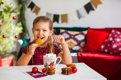 Little girl in red dress eating Christmas cookies with cacao in cup, red Chirstmas decorations around stock photography