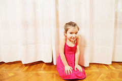 Little girl in red dress on floor Royalty Free Stock Photo