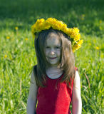 Little girl in a red dress. And a flower wreath Stock Photos