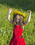 Little girl in a red dress and a flower wreath Stock Images