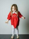 Little girl in red dress frighten photographer. Cute little girl in red dress frighten photographer royalty free stock image