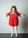 Little girl in red dress frighten photographer. Cute little girl in red dress frighten photographer royalty free stock photo