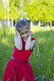 Little girl in a red dress. On a green meadow Stock Photos