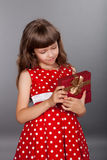 Little girl in red dress holding her present Stock Photos