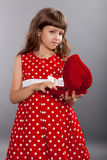 Little girl in red dress holding her present Stock Image