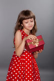 Little girl in red dress holding her present Stock Images