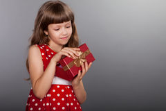 Little girl in red dress holding her present Royalty Free Stock Images