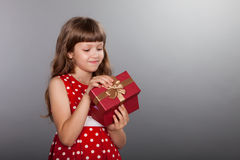 Little girl in red dress holding her present Stock Photography