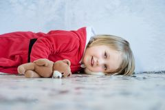 Little girl in red dress at a home interior waiting for Santa.  Royalty Free Stock Photography