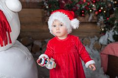 Little girl in red dress at a home interior waiting for Santa. Cute child in the santa claus hat Royalty Free Stock Photos