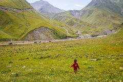 A little girl in a red dress and a knitted cap-strawberry runs on a green field in the mountains. stock photo