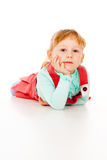 A little girl in a red dress, lying posing Royalty Free Stock Image