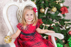 Little girl christmas. Little girl in red dress near Christmas tree with presents and Christmas toy Royalty Free Stock Photography