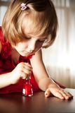 Little girl in a red dress painted nails with nail polish Stock Image