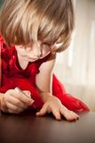 Little girl in a red dress painted nails with nail polish Royalty Free Stock Photography