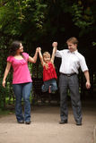 Little girl in red dress with parents in park Royalty Free Stock Images