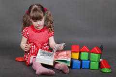 Little girl in red dress sits on floor Royalty Free Stock Image