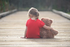 Little girl in a red dress sitting on a boardwalk hugging teddy bear Stock Photography