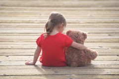 Little girl in a red dress sitting on a boardwalk hugging teddybear Stock Photos