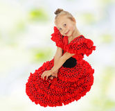 Little girl in a red dress. Little girl sitting on the floor in a bright red dress Stock Images