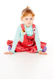 A little girl in a red dress, sitting poses Royalty Free Stock Photo