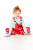 A little girl in a red dress, sitting poses Stock Photo
