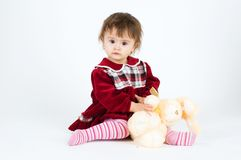 Little girl in red dress sitting with toy bear Royalty Free Stock Photos