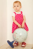 Little girl in red dress stadning at full height. Holding globe in hands indoor. Vertical format Royalty Free Stock Image
