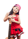 Little girl red dress standing with guitar. Royalty Free Stock Photography