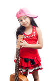 Little girl red dress standing with guitar. Royalty Free Stock Image