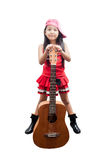 Little girl red dress standing with guitar. Stock Photos