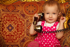 Little girl in red dress talking vintage phone. Royalty Free Stock Images