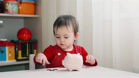A little girl in a red dress throws coins into the piggy Bank HD. 1920x1080 stock video