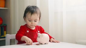 A little girl in a red dress throws coins into the piggy Bank 1080. A little girl in a red dress throws coins into the piggy Bank 1920x1080p HD stock video footage
